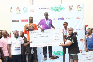 Gov. Ambode and Herbert Wigwe Presenting Abraham Kipton with the $50,000 cheque